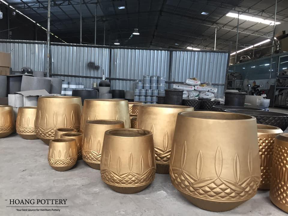 SO IMPRESSIVE: HOANG POTTERY'S COPPER-GOLD PAINTED CEMENT PLANTERS.